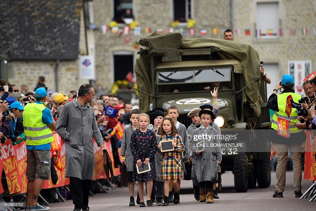Children dressed as 1940s pupils take part in a parade, walking ahead an World War II US army vehicle during the team presentation ceremony in Sainte-Mere-Eglise, Normandy, on July 30, 2016, two days before the start of the 103rd edition of the Tour de France cycling race. The 2016 Tour de France will start on July 2 in the streets of Le Mont-Saint-Michel and ends on July 24, 2016 down the Champs-Elysees in Paris. / AFP / LIONEL