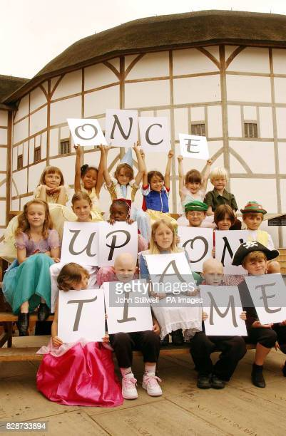 Children dressed as fairy princesses elves and wizards hold up boards to spell the sentence 'once upon a time' at Shakespeare's Globe Theatre in...