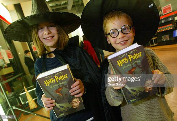 Children dressed as Harry Potter characters hold their justpurchased copy of the Germanlanguage edition of 'Harry Potter and the Order of the...