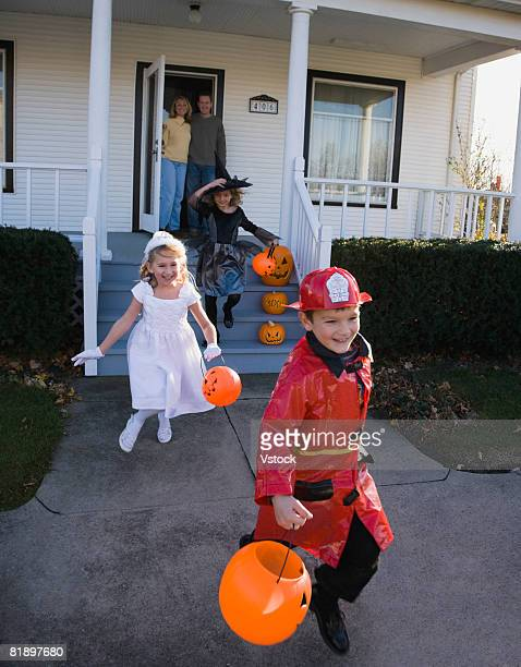 Children dressed in Halloween costumes leaving house