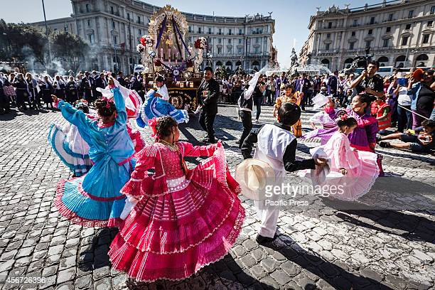 Children dressed in traditional costumes dance while participating in a procession in Rome honoring Peru's most revered Catholic religious icon the...