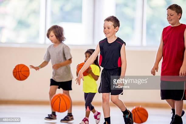 Kinder einen Basketball Dribbeln