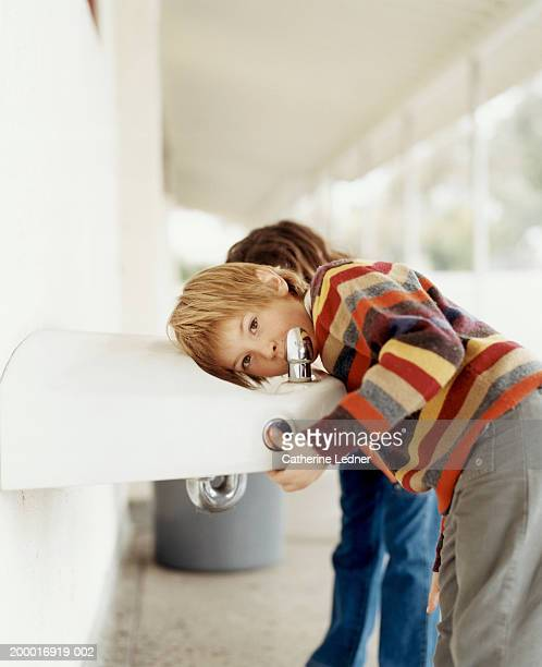 Children (5-7) drinking from water fountain in school hallway