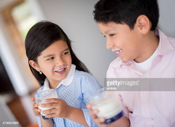 Children drinking milk and leaving a mustache