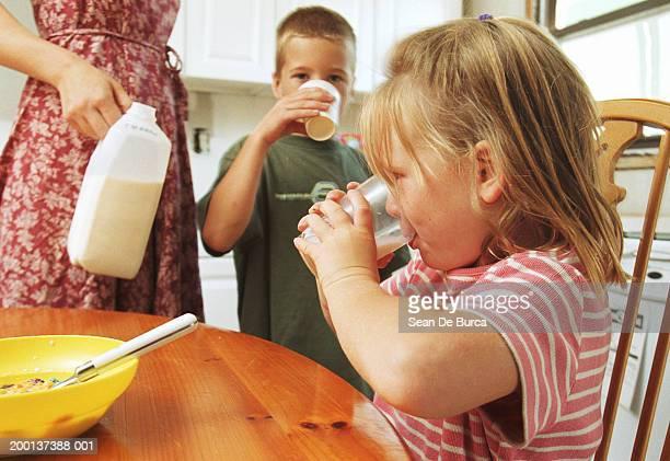 Children (4-8) drinking milk in kitchen, mother beside them