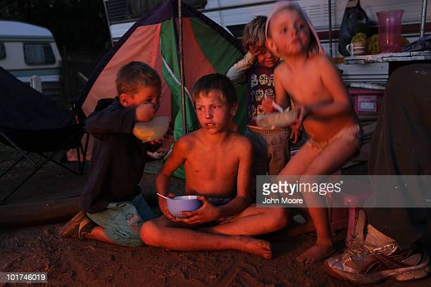 Children eat by the light of a camp fire at a White South African squatter camp on June 7 2010 in Krugersdorp South Africa The municipality tried to...