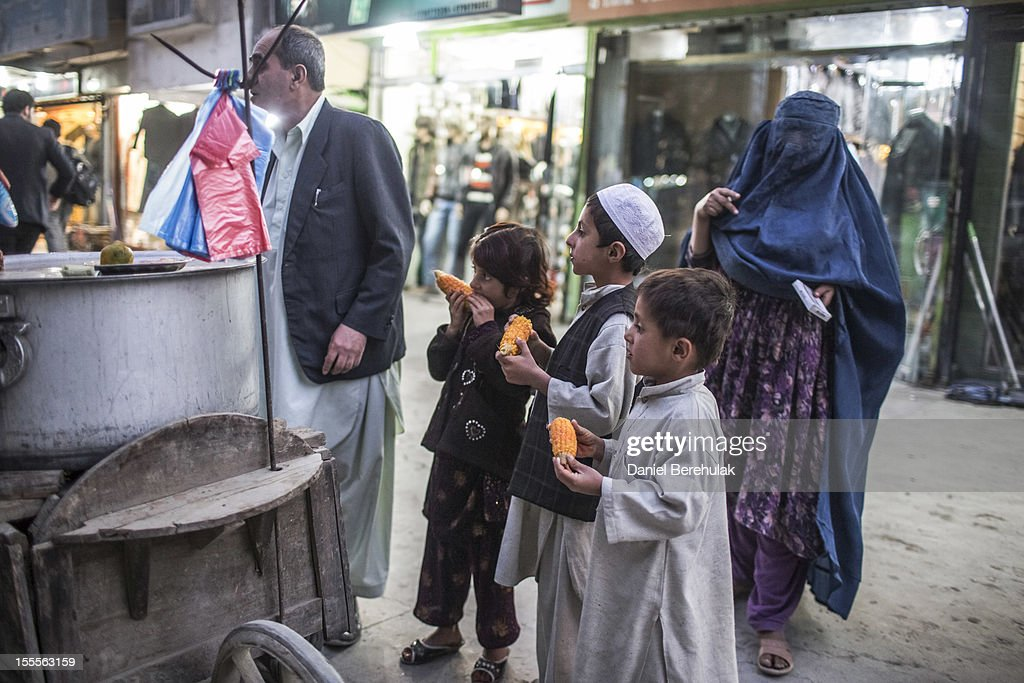 Children eat hot corn bought from a street vendor on November 5, 2012 in Kabul, Afghanistan.