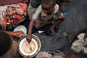 Children eat in a refugee camp for people displaced in conflicts and turmoil that has afflicted Burundi over the last 25 years on June 23 2015 in...