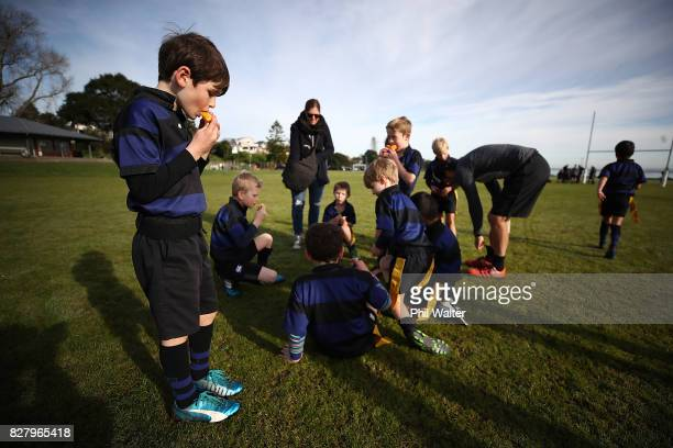Children eat oranges at half time during an Auckland Rippa Rugby Junior Rugby match at Cox's Bay Reserve on August 5 2017 in Auckland New Zealand