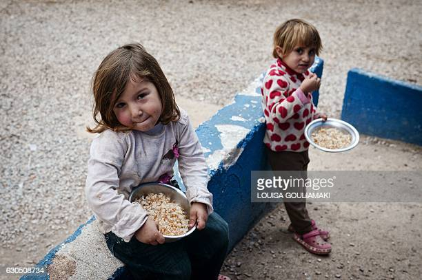 Children eat rice from a meal cooked by chef Talal Rankoussi and volunteers outside the 'Cafe Rits' in Ritsona refugee camp some 80 km north of...