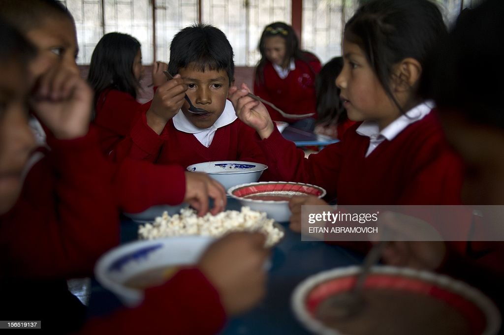 Children eat their soup at a rural school at La Palizada in Tulcan, Carchi province, in Ecuador close to the Colombian border on November 7, 2012. AFP PHOTO/Eitan Abramovich