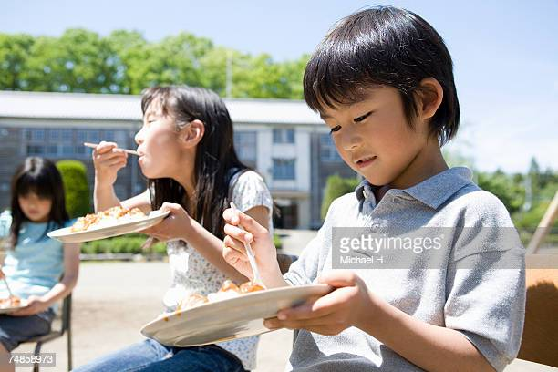 Children (7-9) eating curry in school playground