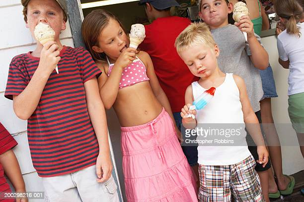 Children (2-12) eating ice creams by tuck shop