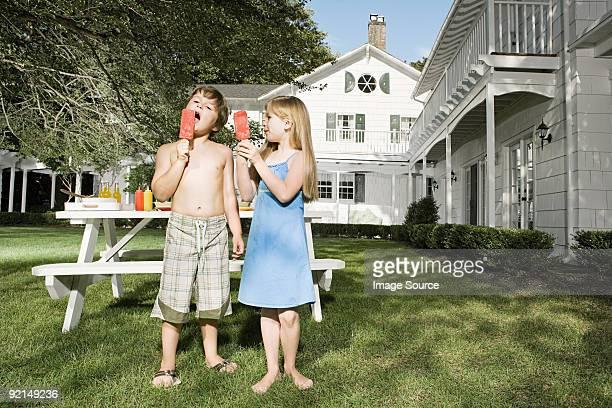 Children eating ice lollies in garden
