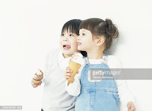 Children (2-5) eating ice-cream, looking away, smiling