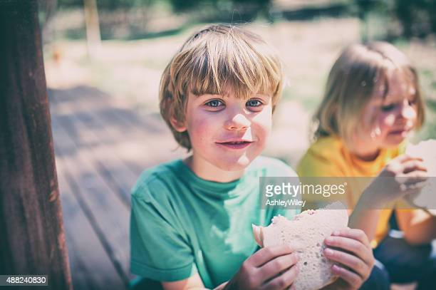 Children eating lunch on a porch step