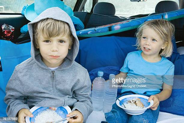 Children eating meal in back of car