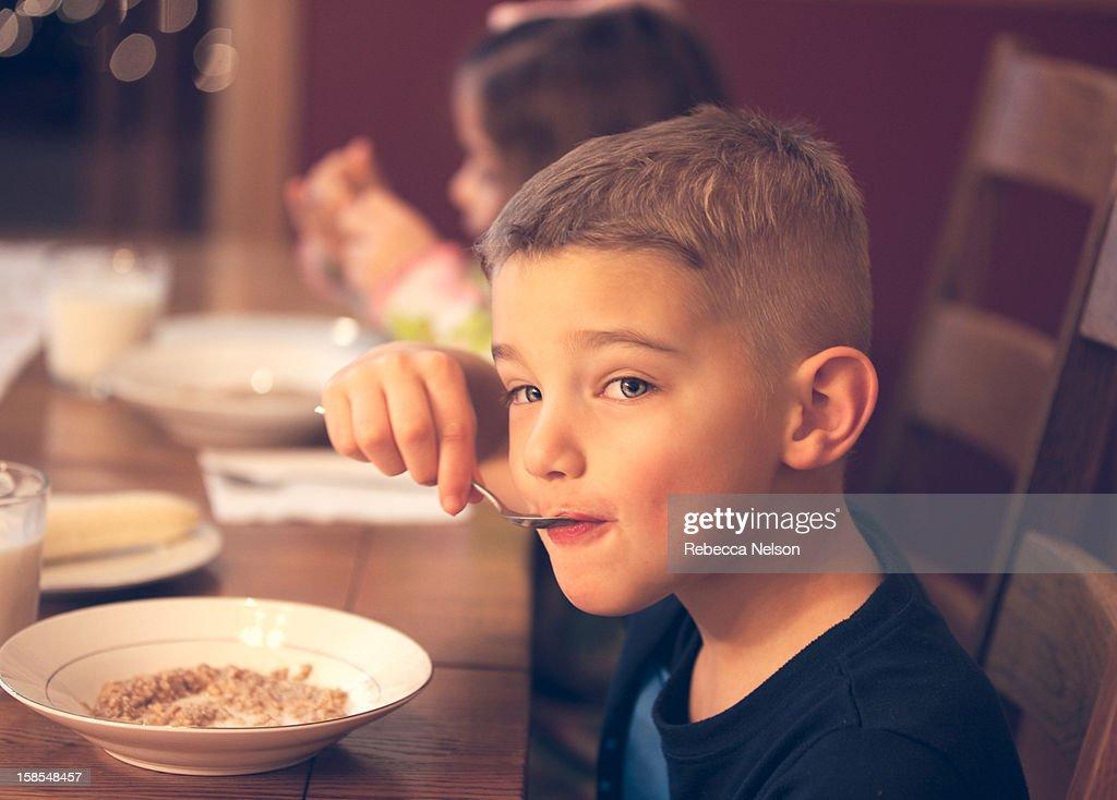 Children eating oatmeal breakfast : Stock Photo