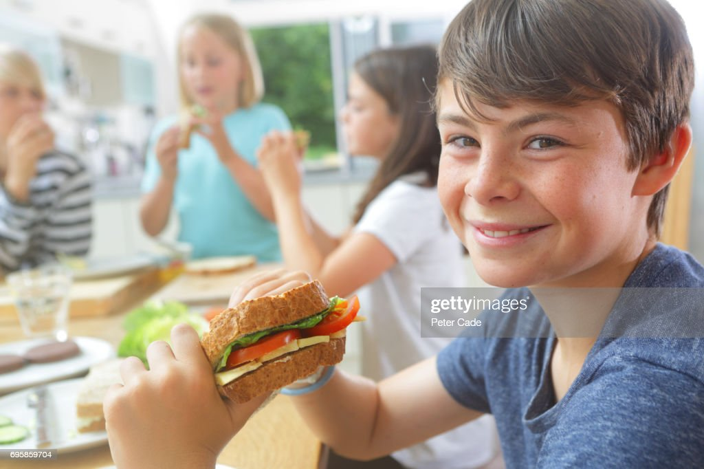 Children eating sandwiches they have made themselves