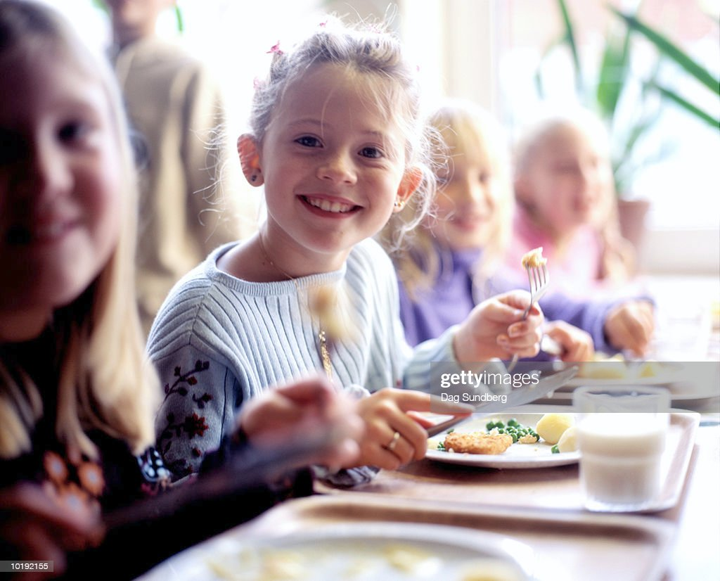 Children (6-8) eating school dinner, portrait : Stock Photo