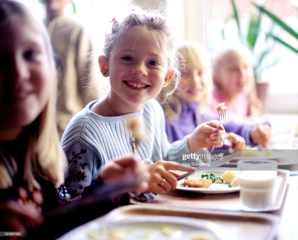 Children (6-8) eating school dinner, portrait