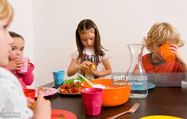 Kinder essen zusammen am Tisch