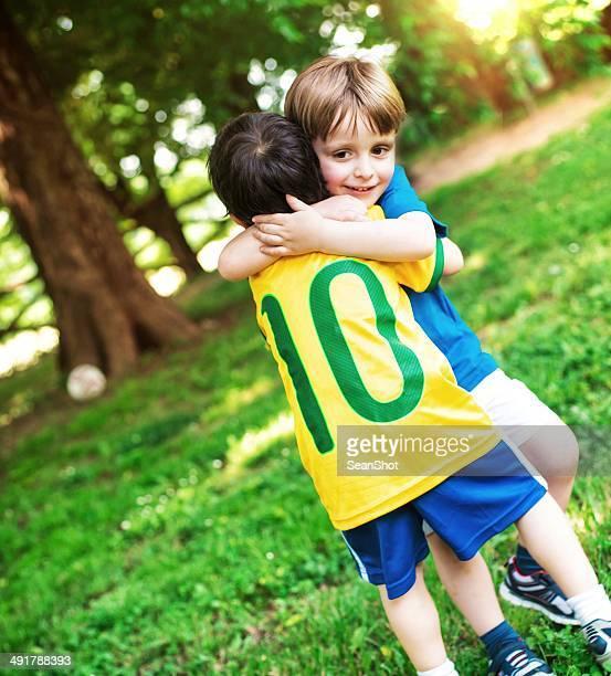 Kinder umarmen einander nach dem Spiel