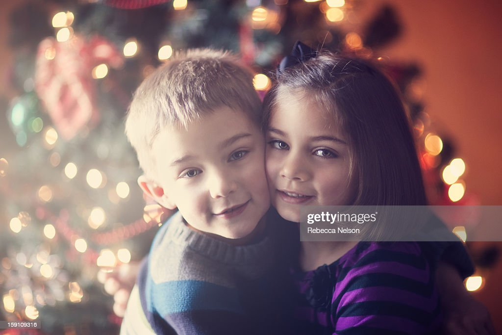 children embracing in front of Christmas tree : Stock Photo