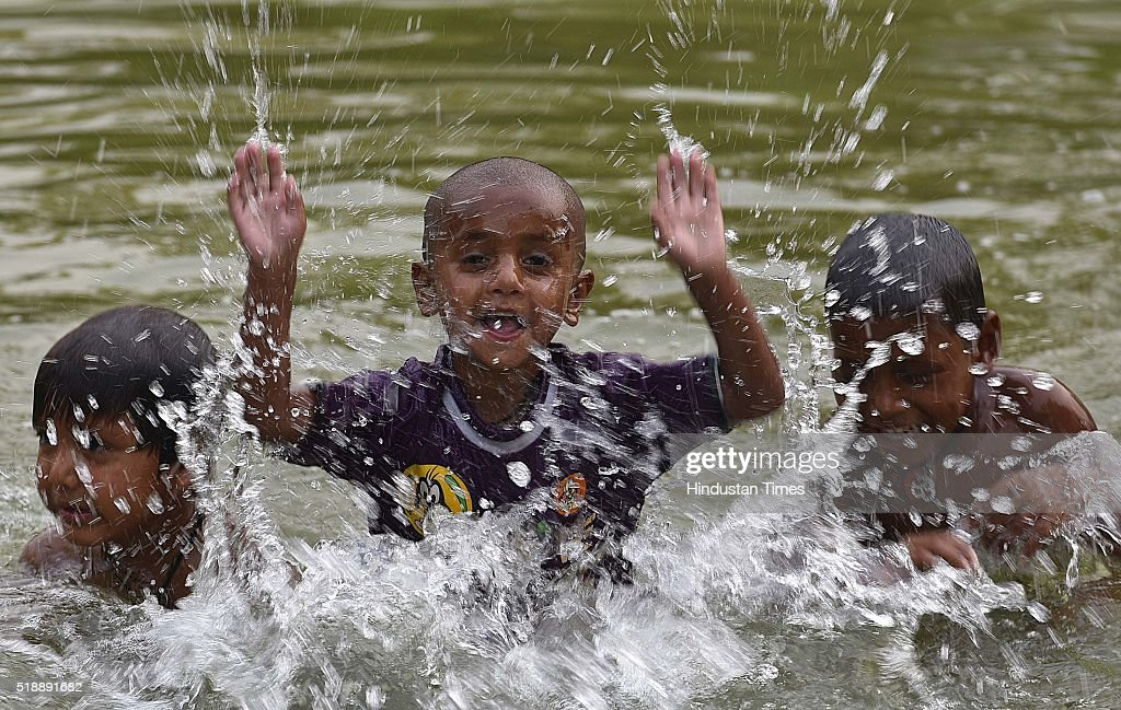 Children enjoy a dip in a pond to beat the heat inside the water pond as the heat wave conditions prevailed in Northern India with the maximum...