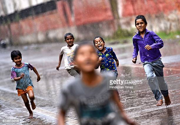 Children enjoy during a light rainfall on March 11 2016 in New Delhi India Light rains lashed the national capital today evening bringing relief from...