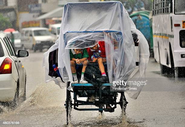 Children enjoy during heavy rain on July 11 2015 in Noida India Heavy rain in Delhi/NCR brings the mercury down and causes water logging in many...