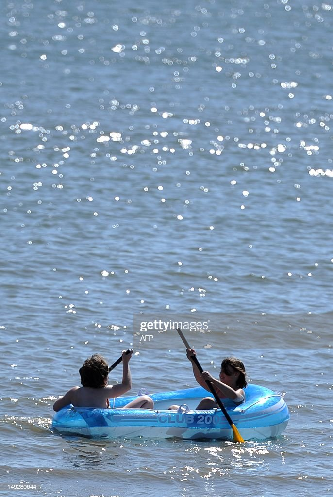 Children enjoy floating on the water surfance with a rubber boat at the North Sea in Wyk on island Foehr, Germany, on July 26, 2012. Meteorologists forecast sunny weather for the upcoming weekend. AFP PHOTO / ANGELIKA WARMUTH GERMANY OUT
