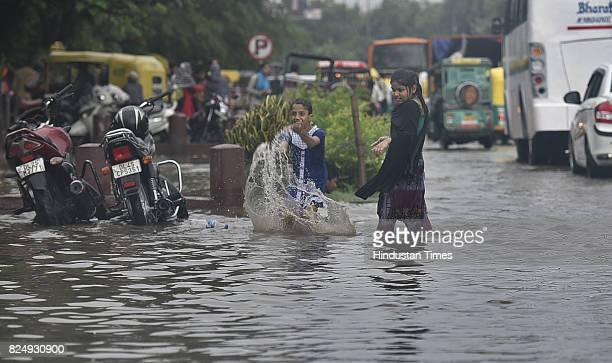 Children enjoy rain water as vehicles wade through logged rain water during a heavy rainfall at Delhi Gate on July 31 2017 in New Delhi India...