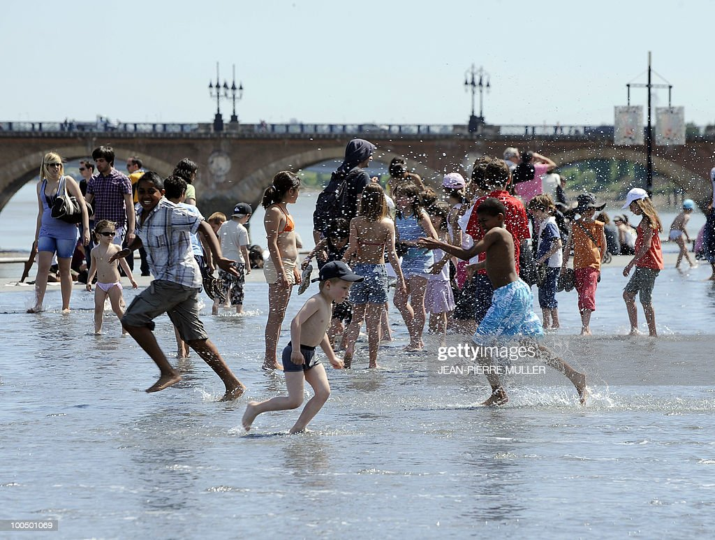 Children enjoy some cool in the water mirror situated on the docks of Bordeaux southwestern France, on April 27, 2010. Temperatures in the the south of France reached today 23 to 27 degrees Celsius.