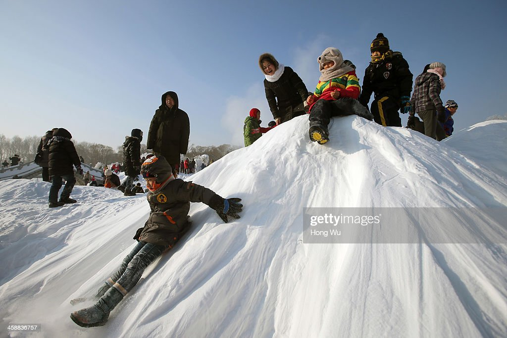 Children enjoy the snow at the 26th Harbin International Snow Sculpture Art Expo in Sun Island park on December 22, 2013 in Harbin, China. The Harbin International Ice and Snow Sculpture Festival is one of the largest ice and snow festivals in the world and is a popular winter destination for both Chinese and foreign visitors.