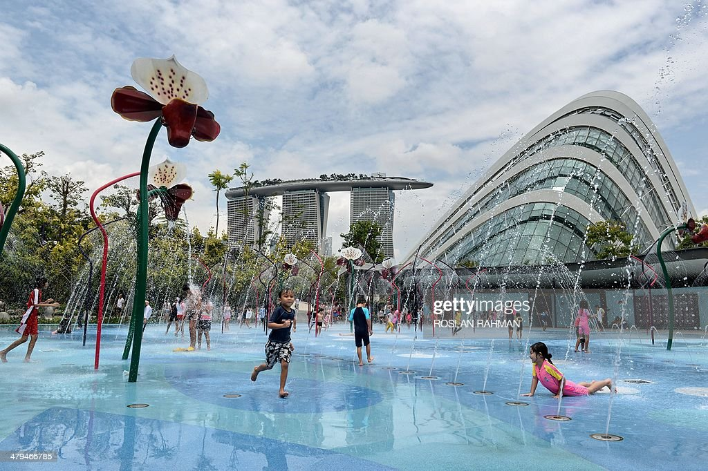 Children enjoy water fountain playground at Garden by the Bay in Singapore on March 19, 2014. The programmable water display is linked to sensors which detect the movement of children to create a corresponding sequence of water effects.