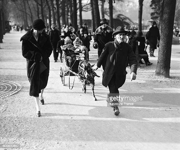 Children enjoying the first days of spring in this goat drawn stagecoach in the Jardin des Tuileries in 1928 in Paris France