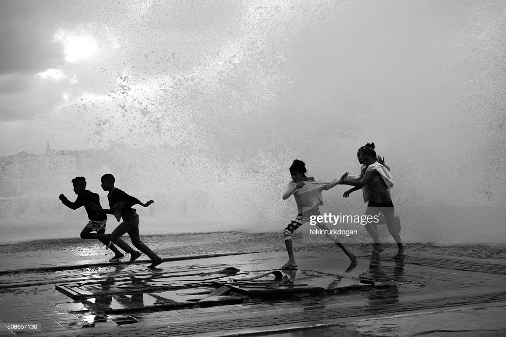 children escape from waves at malecon street of havana cuba : Stock Photo