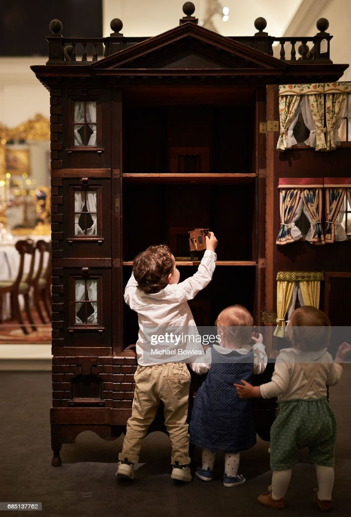 Children explore a large George II mahogany Palladian 'baby' house on display as part of the Ballyedmond Collection at Sotheby's on May 19, 2017 in London, England.