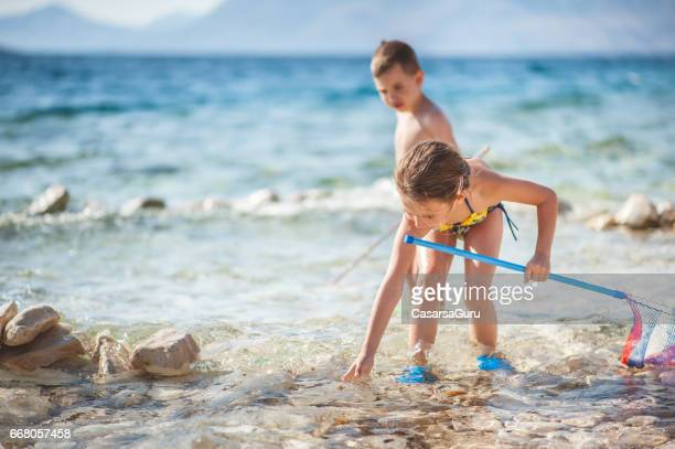 Children Exploring Sea With The Fishing Net