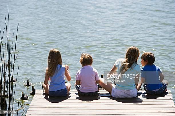 Children feeding ducks on a lake