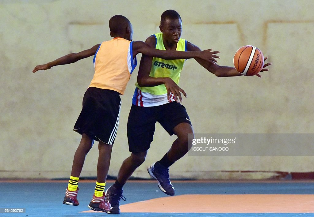 Children fight for the ball during a basketball match of the four days of workshop with the American player Tommy Davis organised by the US embassy at the Felix Houphouet-Boigny University in Abidjan on May 25, 2016. / AFP / ISSOUF
