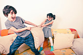 Children fighting over pillow on couch