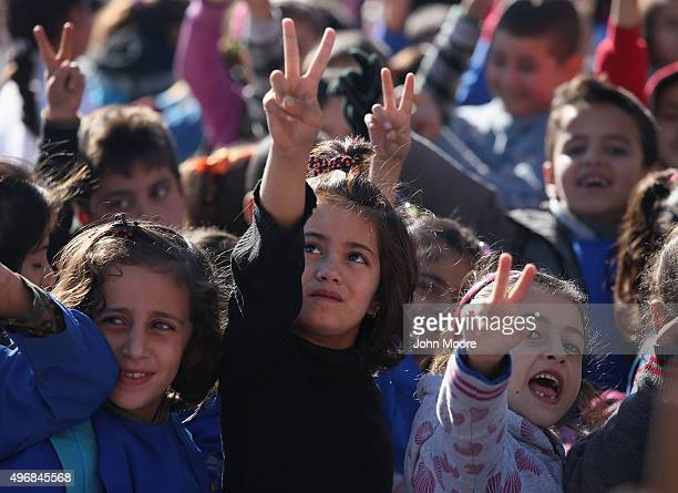 Children flash the victory sign after singing the Rojava anthem at a public elementary school on November 12 2015 in Qamishli Rojava Syria Although...