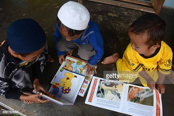 Children flip through books from Ridwan Sururi's horseback mobile library in a concept called Kudapustaka on August 05 2015 in Purbalingga Indonesia...