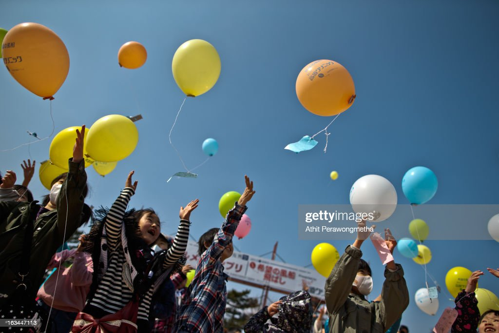 Children float balloons and pay their respects to victims during the second anniversary commemoration of the earthquake and tsunami on March 10, 2013 in Minamisoma, Japan. Japan on March 11 will commemorate the second anniversary of the magnitude 9.0 earthquake and following tsunami, that claimed more than 18,000 lives.