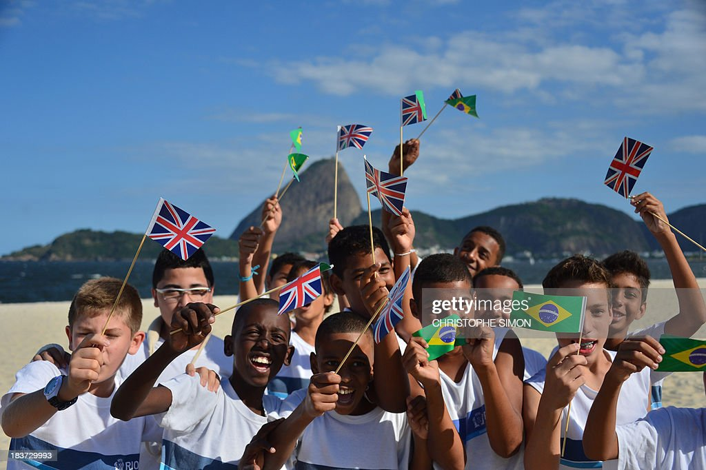 Children flutter Brazilian and British flags during a match between residents of the Rocinha favela and former England Sevens' rugbier, Ollie Phillips, at Flamengo beach in an initiative supported by the Rio 2016 Organizing Commitee's Education Department on October 9, 2013 in Rio de Janeiro, Brazil. AFP PHOTO / CHRISTOPHE SIMON