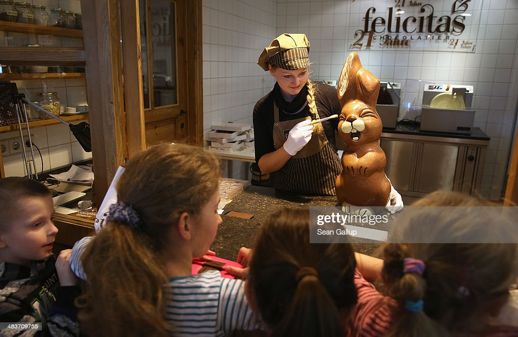 Children from a Polish tour group watch as employee Sandra Jaeckel demonstrates a brush technique on a giant chocolate Easter bunny at Confiserie Felicitas chocolates maker on April 9, 2014 in Hornow, Germany. Easter is among the busiest times of year for the chocolatier, which produces Easter bunnies and eggs in a wide variety of sizes and styles. Founded by Belgian expats Goedele Matthyssen and Peter Bientsman the company will soon celebrate its 21st year.