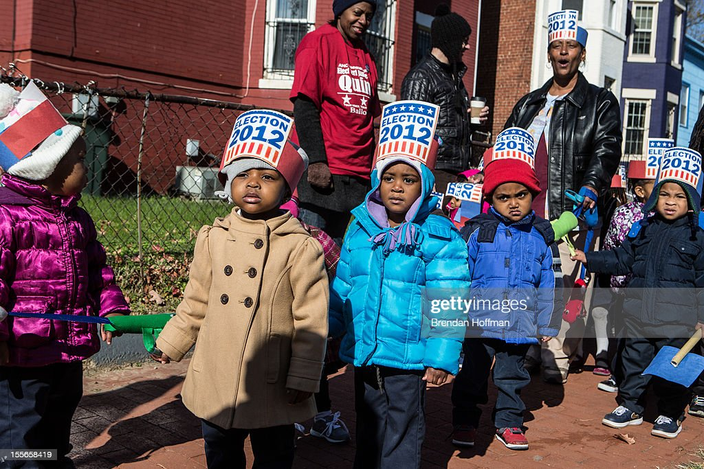 Children from Kingdom Kinds Child Development Center march past a polling station to get out the vote at Dunbar High School on November 6, 2012 in Washington, DC. The latest polls continue to show a tight race between President Barack Obama and Republican challenger Mitt Romney.