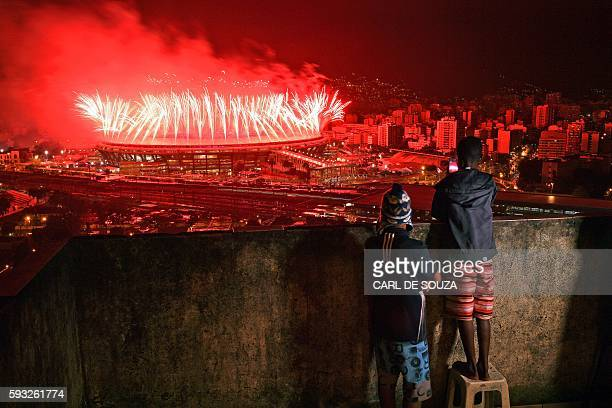 TOPSHOT Children from Mangueira favela watch fireworks over Maracana Stadium during the Rio 2016 Olympics Games closing ceremony in Rio de Janeiro on...